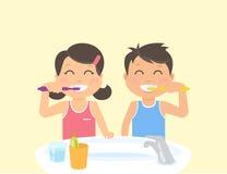 刷牙的愉快的孩子站立在卫生间里在水槽附近 免版税图库摄影