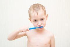 刷他的在的白肤金发的美丽的男孩牙 免版税库存图片