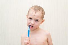 刷他的在的白肤金发的美丽的男孩牙 库存图片
