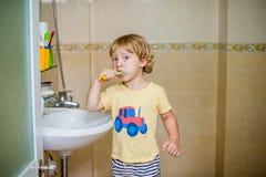 刷他的牙的小男孩在卫生间里 库存照片