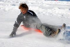 刹车在小山雪撬下的男孩sledding 图库摄影