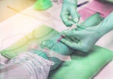 刺在胳膊患者的两次曝光护士针注射器有有玻璃和血液图处方纸的听诊器的 库存图片