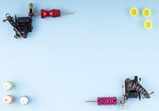 刺字有三个瓶的机器墨水和三个墨水容器在蓝色背景 免版税图库摄影