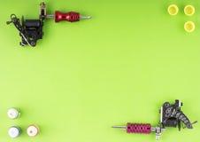 刺字有三个瓶的机器墨水和三个墨水容器在绿色背景 图库摄影