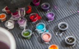 刺字艺术家混合的颜色入墨水的小杯子 库存照片