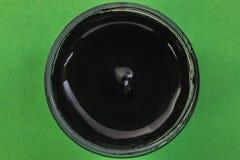 刺激与在一个绿色背景特写镜头的黑树胶水彩画颜料 图库摄影
