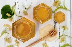 刺激与在老土气木桌上的蜂蜜和菩提树花 免版税图库摄影