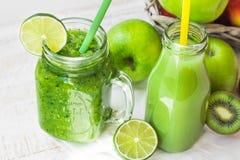 刺激有绿色菜圆滑的人和果汁的杯子在有秸杆的,苹果,石灰,猕猴桃瓶,户外 免版税图库摄影
