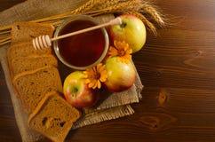 刺激用蜂蜜、黑麦面包、苹果、黄色雏菊和耳朵在袋装,木桌 图库摄影