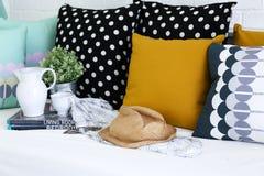 刺激,咖啡杯和书与五颜六色的枕头在背景中 免版税图库摄影