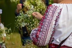 刺绣的妇女编织花花圈在伊冯Kupala传统宴餐的  免版税库存照片