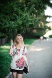 刺绣的白肤金发的女孩在步行的一棵毛皮树附近 免版税库存图片