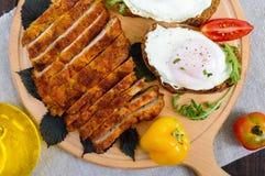 剁炸肉排,多士用鸡蛋,在一个木板的新鲜的蕃茄片断在黑暗的背景 免版税库存照片