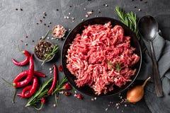 剁碎 与成份的绞肉烹调的在黑背景 库存照片