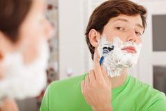 剃在卫生间里的人 免版税库存图片