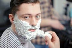 剃在理发店的客户 免版税库存图片