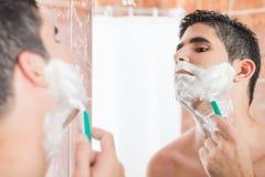 剃在镜子前面的赤裸上身的西班牙人 图库摄影