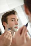 剃在镜子前面的年轻人 免版税库存图片