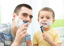 剃在镜子的父亲 孩子儿子仿效父亲 免版税库存图片