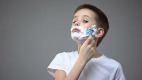 剃滑稽的小男孩,假装是成人,复制的父亲行为 股票视频