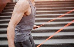 削减为跳使用一条绳索的观点的一个肌肉人 他的肌肉紧张 他做着非常密集的锻炼 库存照片