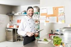 削尖刀子的刀片微笑的厨师在厨房里 库存照片
