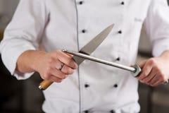 削尖刀子的厨师在商业厨房里 免版税库存照片