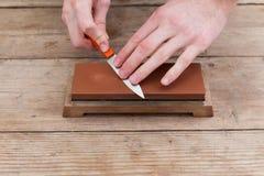 削尖有一块磨刀石的刀子在木背景 顶视图 免版税库存照片