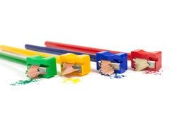 削尖有五颜六色的铅笔削片的绿色,黄色,蓝色和红色铅笔刀宏观射击铅笔隔绝在白色 库存照片