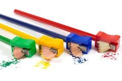 削尖有五颜六色的铅笔削片的绿色,黄色,蓝色和红色铅笔刀宏观射击铅笔隔绝在白色 免版税库存照片