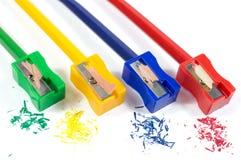 削尖有五颜六色的铅笔削片的绿色,黄色,蓝色和红色铅笔刀宏观射击铅笔隔绝在白色 库存图片