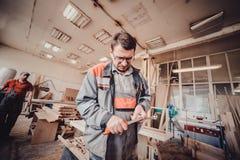 削尖有小折刀的木匠杂物工铅笔在木制品车间桌上 库存照片