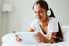 前使用片剂个人计算机的青少年的女孩 免版税库存图片