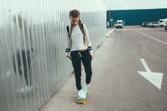 前在城市街道上的青少年的溜冰者 免版税库存图片