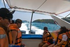 前往有泳装的海岛的速度小船的人们 图库摄影