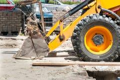 前方地球搬家工人和装载者推土机挖掘机在街道上的建筑机械铁锹和轮胎  库存照片
