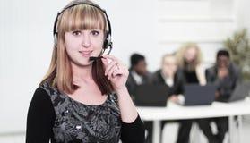 前景是电话中心的一个成功的女雇员 图库摄影