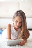 前有片剂个人计算机的青少年的女孩 免版税库存图片