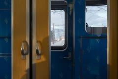 前窗在蓝色里面的雪视图和黄色训练 免版税库存照片