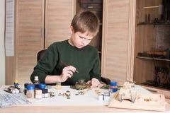 前装配和绘塑料式样坦克的青少年的男孩在workp 库存图片
