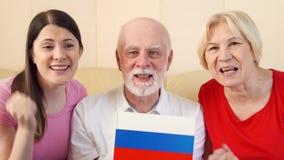 前辈和青少年的女儿观看的橄榄球赛 庆祝赢取在冠军的俄国爱好者 股票视频