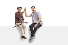 前辈和高fiving一个年轻的人 免版税图库摄影