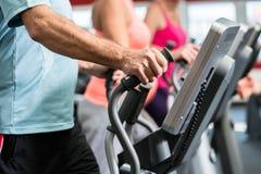 前辈在与个人教练员的发怒教练员训练在健身房 免版税库存照片