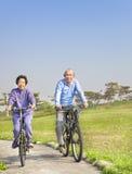 前辈在公园耦合骑自行车 免版税库存照片