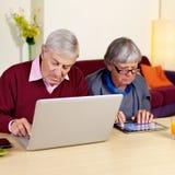 前辈在家退休了运作在垫和个人计算机的夫妇 库存照片