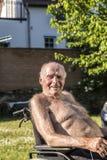 前辈在椅子坐在庭院里 库存照片