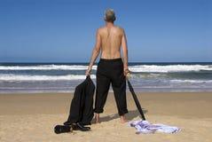 前辈退休了在一个热带海滩的商人脱下衣服的身分,退休自由概念 免版税库存图片