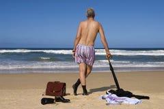 前辈退休了脱下衣服在加勒比海滩,退休自由逃命概念的商人 库存照片