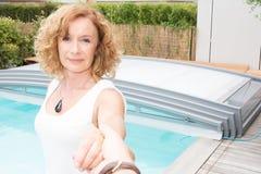 前辈退休的妇女做与电话的selfie在水池 库存照片