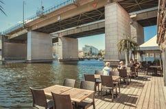 前辈,刷新和喝在河餐馆的青年人在具体桥梁附近 库存图片